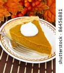 Thanksgiving pumpkin pie in a plate with autumn leaves behind - stock photo