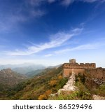 the great wall of china in autumn against a blue sky - stock photo