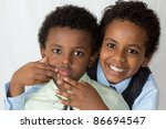 Portrait of two brothers, one trying to cheer up the other - stock photo