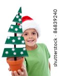 Happy kid in santa hat holding christmas decoration fir tree - closeup, isolated - stock photo