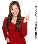 showing woman presenting blank gift card sign. Happy smiling Asian woman in red winter sweater isolated on white background. - stock photo