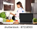 cooking and computer laptop concept. Blank pc monitor screen in focus with cooking woman in kitchen. - stock photo