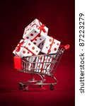 Small photo of shopping cart ahd christmas gift on the red