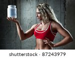Young muscular woman with sports nutrition. - stock photo