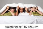 Sleepover party bedtime fun for three happy beautiful teenage girl friends, a mixed race african american, oriental Japanese and blonde caucasian school mates laughing under bed covers. - stock photo