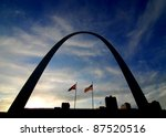 Silhouette of St. Louis Arch and city skyline with flags, sky and clouds - stock photo