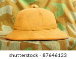 Retro helmet for tropical destination on a camouflage fabric. - stock photo