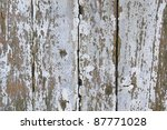 full frame abstract detail of a rundown wooden facade with flaking paint and fissures - stock photo