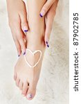 body part shot of beautiful healthy young woman's leg and manicured hands. heart is drawn with white care cream on pedicured foot - stock photo