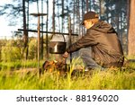 A young man prepares a hot meal in a cauldron on a fire outdoors - stock photo