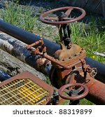 Metal pipes labeled fuel oil with a large valve with green grass in the background. - stock photo