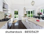 Stock photo stylish open plan kitchen with stainless steel appliances and dining area overlooking a pool and 88505629