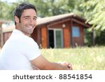 Smiling Man Sitting In Front O...