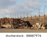 Compressed piles of metal scrap stacked by a rustic wooden fence on a sunny day with clouds. - stock photo