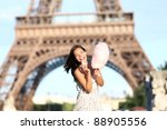 Paris Eiffel Tower woman smiling happy and cheerful eating cotton candy in front of Eiffel Tower in Paris, France. Cute Asian / Caucasian girl. - stock photo