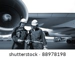 Small photo of two airplane mechanics with giant jet engine in background, blue toning idea.