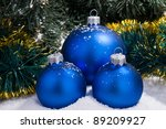 blue spheres on snow under a fur-tree - stock photo
