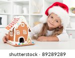 My christmas gingerbread cookie house - little girl in the kitchen at holidays - stock photo