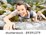 happy woman climbs a rock while ... | Shutterstock . vector #89391379
