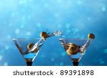 glasses  with martini and green olives on a blue background - stock photo