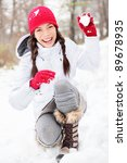 winter woman playing in snow throwing snowball at camera smiling happy having fun outside on snowing winter day. Beautiful joyful multicultural Asian Caucasian girl outdoors. - stock photo