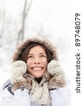 winter woman in snow looking up at copy space outside on snowing cold winter day. Portrait multiethnic Caucasian Asian female model outside in first snow - stock photo