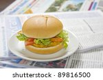 big hamburger on newspaper - stock photo