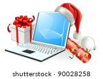 Christmas laptop computer with Santa hat, gift cracker and bauble - stock photo