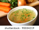 A picture of a bowl of traditional chicken soup served in a bowl over vegetable background - stock photo