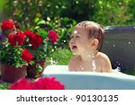 cute funny small baby boy bathing outdoor on green lawn among flowers - stock photo