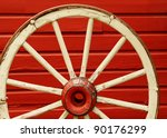 Old weathered wagon wheel leaning against red wall - stock photo