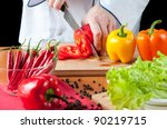 Preparing food: chef cutting a red bell pepper - stock photo