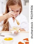 Sweet morning - little girl preparing to eat honey on bread, focus on the hand - stock photo