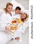 Happy morning and healthy food - mother bringing breakfast to bed for her kids - stock photo