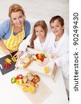 Woman and kids preparing breakfast together - stock photo