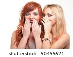 two happy young girlfriends blond and ginger talking white background - society gossip, rumor, rumour - stock photo