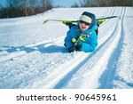 Young boy with cross-country skis lying on snow and smile - stock photo