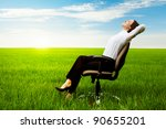 businesswoman relaxing on chair over green meadow - stock photo