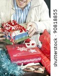 Small photo of Close-up of a man surrounded by the accoutrement of christmas present wrapping.