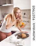 Young pregnant blonde woman eating cake in kitchen - stock photo