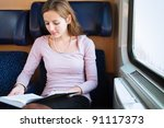 Young woman reading a book while on a train - stock photo
