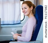 Young woman traveling by train, holding her train ticket, smiling - stock photo