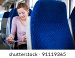 Young woman using her tablet computer while traveling by train - stock photo