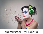 portrait of a clown-girl blowing the tinsel - star. - stock photo