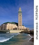 View of Hassan II Mosque and Minaret in Casablanca, Morocco with waves crashing its walls - stock photo