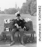 Man feeding pigeons on park bench - stock photo