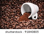 Cup with heap of coffee beans background - stock photo