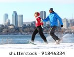Happy couple snowshoeing running in montreal with cityscape skyline and river st. Lawrence in background. Healthy lifestyle photo from Montreal, Quebec, Canada. - stock photo