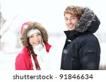 Winter people. Young couple in snow outdoor on winter day. Caucasian man, Asian woman in their twenties. - stock photo