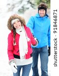 Happy winter couple walking outdoor in snow smiling happy. Beautiful young multi-racial couple, Asian woman, Caucasian man. - stock photo